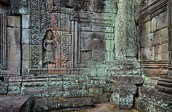 Inner courtyard of Bantay Kdei temple in soft light of dawn showing female figure, floral carvings, stone construction and pillar in soft tones of green, pink and blue from mossy growth