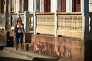 A woman walks down a street in Baracoa, Cuba on Monday July 14, 2008.