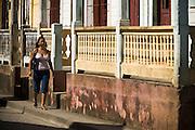 A woman walks down a street in Baracoa, Cuba on Monday July 14, 2008.