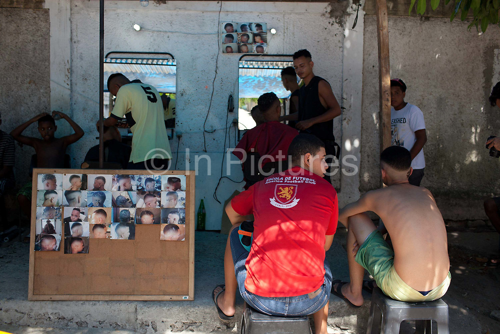 Two 2 young Brazilian men sitting on a bench waiting to have their hair cut. Young independent barber shop hair stylist in the street for the young people guys of Vila Valquiere, West Zone Zona Oueste, Rio de Janeiro