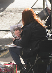 A crew member holds a photo of actor Benedict Cumberbatch who has been shooting scenes in Glasgow which was transformed into New York City for filming of the TV show Melrose.