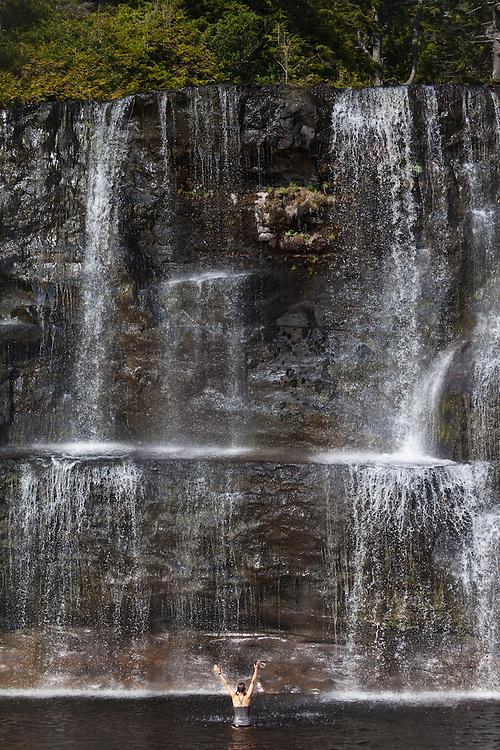 A woman stands below Tsusiat Falls, West Coast Trail, British Columbia, Canada.