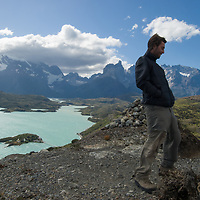 A hiker braves Patagonian winds atop a small peak overlooking Lake Pehoe and the Towers of Paine, Torres del Paine National Park, Chile.