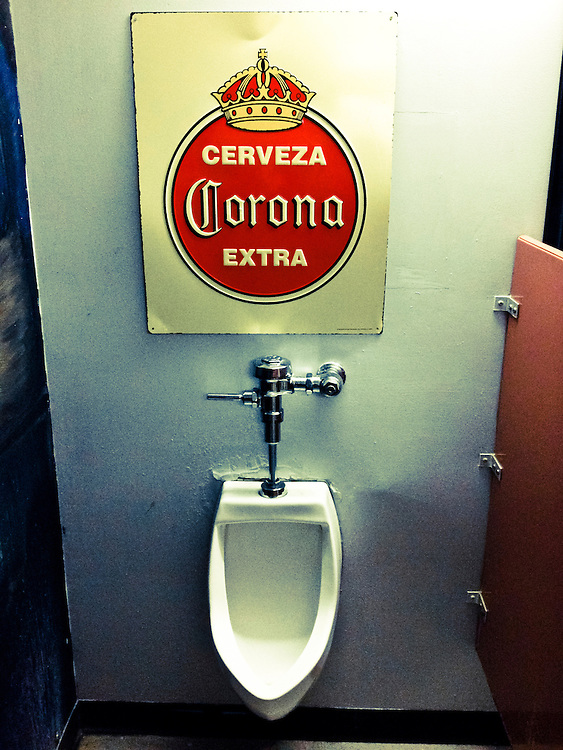 Urinal in a bar with a Corona beer sign hung above it.