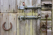 Detail of ramshackle stable outbuilding in Kent countryside. On the fading and green door panels, we see the sliding locks without padlocks and rusting rings and fittings. A rusted horseshoe has also been nailed to the lower door and a single autumn leaf has lodged at the top. The stable is in a rural part of Kent, known as the Garden of England due to its fertile soils and temperate southern climate.