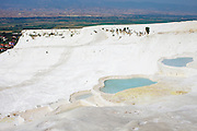 View of the travertine terraces at pamukkale. The hard, white mineral deposits, which from a distance resemble snow, are caused by the high mineral content of the natural spring water which runs down the cliff and congregates in warm pools on the terraces. This is such a popular tourist attraction that strict rules had to be established in order to preserve its beauty, which include the fact that visitors may no longer walk on the terraces. Those who want to enjoy the thermal waters, however, can take a dip in the nearby pool, littered with fragments of marble pillars.