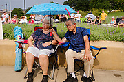 24 JULY 2021 - DES MOINES, IOWA: A couple uses an umbrella to protect them from the sun during the World Wide Freedom Rally in Des Moines. More than 200 people showed up at the Iowa State Capitol Saturday for the World Wide Freedom Rally. The protesters called for governments everywhere to respect five important freedoms: Freedom of Speech, Movement, Choice, Assembly, and Health. Their main concern Saturday was Freedom of Health, which they said included the freedom to refuse vaccinations and the freedom to refuse to wear face masks, even during the time of airborne viruses.       PHOTO BY JACK KURTZ