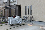 Covered motobike and cycles in suburban driveway. Kyoto, Japan.