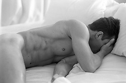 Naked young man covering his face while in bed