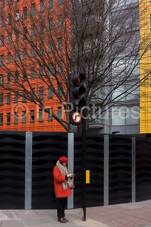 Woman wearing matching red beret and coat stands beneath orange and yellow architecture. The lady stands attending to her smartphone on a street corner in central Londo. Her coat matches the red of the modern architecture behind as well as the yellow of the crossing control panel of the right-hand yellow. The modernity is seen as an echo of colour and tone - of a coincidental urban landscape in the capital.
