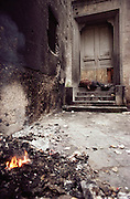 Homeless man sleeps in the doorway of an abandoned building with a trash fire burning in the foreground. Naples, Italy.