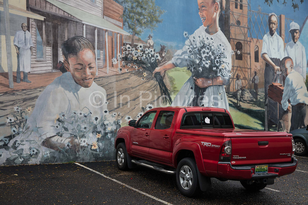 Mural in downtown Dothan carpark, sponsored by a local church, highlighting the history of the area on 5th March 2020 in downtown Dothan, The Peanut Capital of the World, Alabama, United States of America. Most of the murals commemorate something about this section of Alabama, known as the Wiregrass area. Wes Hardin has been commissioned to tell the story of the industrial growth of Dothan, where he makes his home. He has painted the stories of turpentine and logging, of cotton and railroads. He has been commissioned to tell the story of soda fountains and businesses, of Sherman Rose, who trained the Tuskegee Airmen, and of musical legends in the Wiregrass.