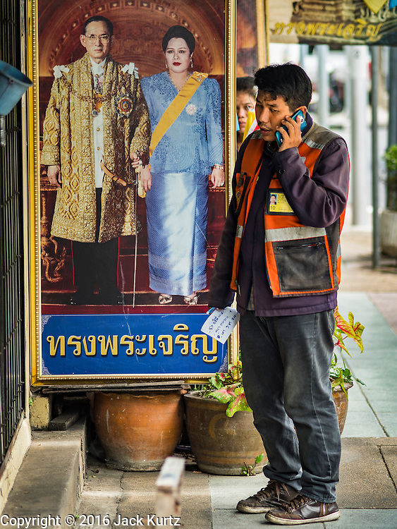 10 AUGUST 2016 - BANGKOK, THAILAND: A motorcycle taxi driver uses his cell phone in front of a portrait of Bhumibol Adulyadej, the King of Thailand, and his wife, Queen Sirikit. Thais are preparing for the Queen's birthday. Queen Sirikit of Thailand, was born Mom Rajawongse Sirikit Kitiyakara on 12 August 1932. She married  Bhumibol Adulyadej, King of Thailand (Rama IX) in 1950. He is the longest serving monarch in the world and she is longest serving consort of a monarch. Her birthday, like the King's Birthday (which falls on Dec. 5),  is a national holiday in Thailand. Her birthday, August 12, is also celebrated as Mothers' Day in Thailand. Thais hang portraits of Queen Sirikit in their homes and fly her royal flag on her birthday.        PHOTO BY JACK KURTZ