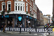Environmental activists from Extinction Rebellion hold a banner reading No Future In Fossil Fuels during the first day of Impossible Rebellion protests on 23rd August 2021 in London, United Kingdom. Extinction Rebellion are calling on the UK government to cease all new fossil fuel investment with immediate effect.