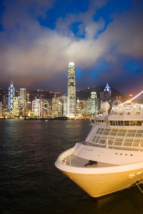 Cruise Liner moored on the Kowloon side of Hong Kong Harbour. Many cruise ships pass through the waterway or moor for the night to offer passengers a chance to watch the dramatic skyline develop and light up. Clouds form over the peak at nightfall and collect over Hong Kong's dramatic night skyline. Many of Hong Kong's distinctive buildings line up including the once dominant Bank of China building. Two International Finance Centre now towers over the skyline at 88 stories 415m tall, lighting up the clouds it nearly reaches. A classic blue Hong Kong sky forms a backdrop for the forming clouds.