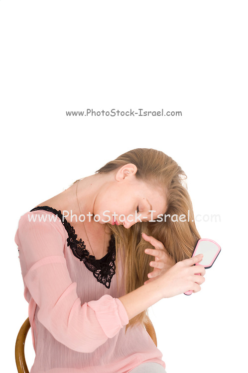 young teen brushes her hair On white Background