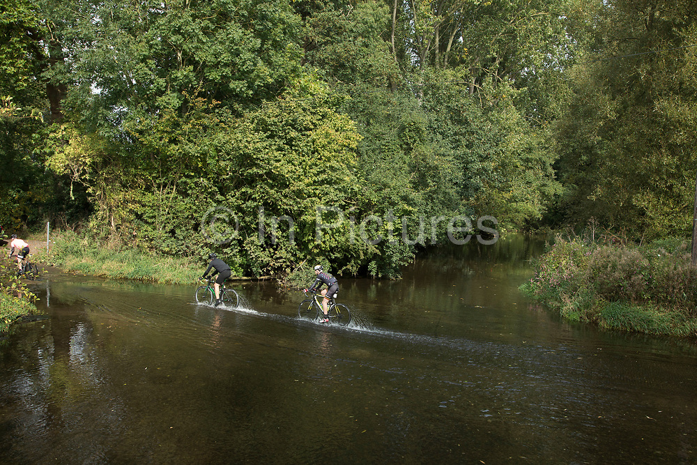Cyslists cycle through deep water of a ford from the overflowing River Arrow in British countryside in September near to Coughton, England, United Kingdom.
