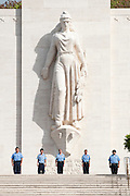 Five young cadets stand at attention under the statue at the Punchbowl National Cemetery of the Pacific on Memorial Day.