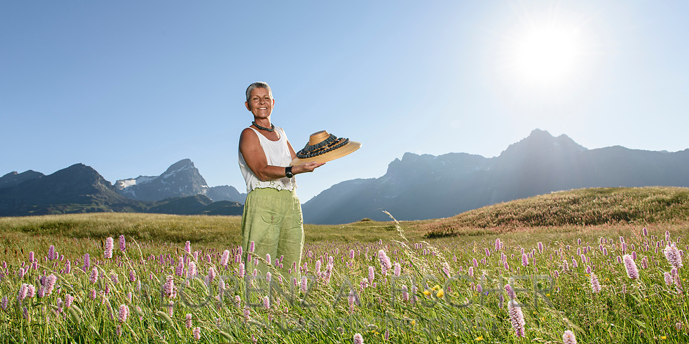 Doris Guetg is is posing in a field of common bistort with some of her stone art jewelleries on the Alp Flix on a nice and cristal clear summer evening in July with the Piz Scalotta, Platta, Forbesch and Arblatsch in sight, Parc Ela, Grisons, Switzerland
