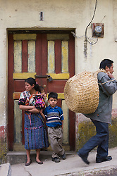 Woman with children standing in front of colorful doorway as people pass by, Chichicastenango, Guatemala