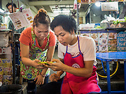 26 MAY 2015 - BANGKOK, THAILAND:  Street food vendors on Sukhumvit Soi 38 check their smart phone while they wait for customers. Soi 38 is one of the most popular street food areas in Bangkok. The food carts and small restaurants along the street have been popular with tourists and Thais alike for more than 40 years. The family that owns the land along the soi recently decided to sell to a condominium developer and not renew the restaurant owners' leases. More than 40 restaurants and food carts will have to close. The first wave of closings could start as soon June 21 and all of the restaurants are supposed to close over the next several months.    PHOTO BY JACK KURTZ