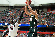 29 MAR 2015: Travis Trice (20) of Michigan State University shoots over Montrezl Harrell (24) of the University of Louisville during the 2015 NCAA Men's Basketball Tournament held at the Carrier Dome in Syracuse, NY. Michigan State defeated Louisville 76-70 to advance. Brett Wilhelm/NCAA Photos