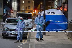 © Licensed to London News Pictures. 10/04/2021. London, UK. Forensic investigators at the scene after a 17-year-old boy was fatally stabbed in Sydenham. Police were called to Hazel Grove, junction with Sydenham Road, at 19:19BST on Saturday, 10 April after reports of a male lying injured on the ground. Officers attended with medics from the London Ambulance Service and the London Air Ambulance. They found a 17-year-old male who had been stabbed. Despite the best efforts of the emergency services, he was pronounced dead shortly after 20:00BST. Photo credit: Peter Manning/LNP