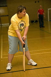 Day service user with learning disability playing indoor cricket in the gym,