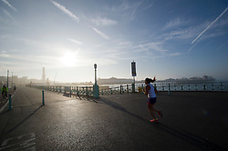 © London News Pictures. 24/09/2013 . Brighton, UK.  A woman running in front of Brighton Pier shrouded in fog early morning on the day Ed MIliband makes his keynote speech at the 2013 Labour Party Conference in Brighton. . Photo credit : Ben Cawthra/LNP