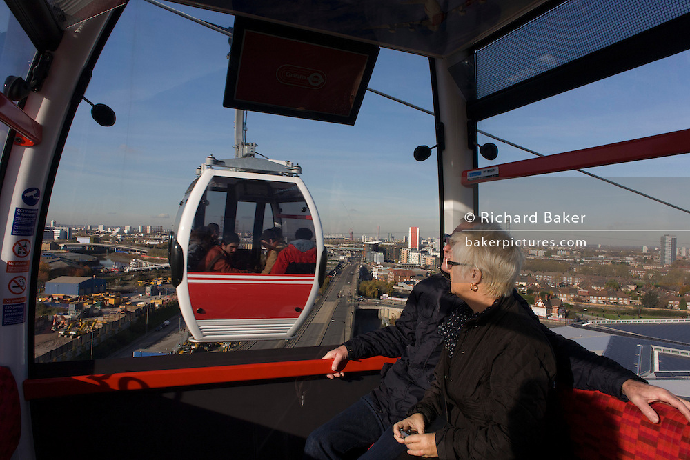 Passengers ride in a gondola on a journey over the River Thames on the Emirates Cable Car, from Royal Docks towards the Greenwich Peninsular. There are 34 gondolas, each with a maximum capacity of 10 passengers. The Emirates Air Line (also known as the Thames cable car) is a cable car link across the River Thames in London built with sponsorship from the airline Emirates. The service opened on 28 June 2012 and is operated by Transport for London. The service, announced in July 2010 and estimated to cost £60 million, comprises a 1-kilometre (0.62 mi) gondola line that crosses the Thames from the Greenwich Peninsula to the Royal Docks. ..