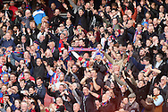 Crystal Palace fans celebrate after the final whistle as they see their team secure a 1-1 draw. Barclays Premier league match, Arsenal v Crystal Palace at the Emirates Stadium in London on Sunday 17th April 2016.<br /> pic by John Patrick Fletcher, Andrew Orchard sports photography.