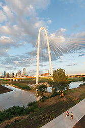 Cyclists seen from Continental Avenue Bridge with Margaret Hunt Hill Bridge in background, Trinity River, Dallas, Texas, USA.