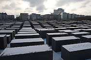 A snow-covered section the Holocaust memorial which stands on former no-mans land along the route of the former Berlin Wall near Potsdamer Platz in the city centre. The route of the Wall, which stood from 1962-1989, has been developed into the 'Mauerweg,' a thoroughfare which traces most of the route of the Wall which encircled the city and divided it into East and West Berlin during the Cold War. In the years following the 1989 civil uprising in the German Democratic.Republic, most of the Wall was removed as part of the reunification strategy which united the pro-Soviet DDR and the Federal Republic of (West) Germany.