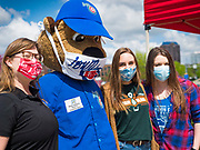 """06 MAY 2020 - DES MOINES, IOWA: """"CUBBIE,"""" the mascot for the Iowa Cubs, wears a face mask poses for a photo with workers from Cedar Ridge Winery and Distillery during a distribution of hand sanitizer at Principal Park, the stadium for the Iowa Cubs, the minor league baseball team affiliated with the Chicago Cubs. Two months after the start of the COVID-19 pandemic Iowa retailers still can't keep everyday items like hand sanitizer, toilet paper, and alcohol based cleaning supplies in stock. Many of the artisan distilleries in Iowa have started making and distributing free hand sanitizer.      PHOTO BY JACK KURTZ"""