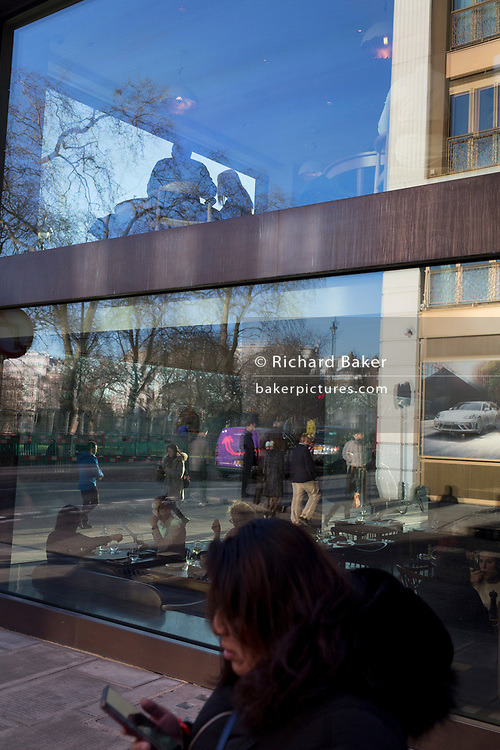 With a Porsche luxury car ad reflected in a restaurant window, customers enjoy fine dining on the corner of Piccadilly and Clarges Street W1, on 20th January 2020, in London, England.