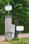 "A white wooden gate and a stone gate post with signs saying Vieux Chateau Certan and ""Entree du Chateau a 100 m"" (Entry to the chateau at 100 metres to the right)  Pomerol  Bordeaux Gironde Aquitaine France"