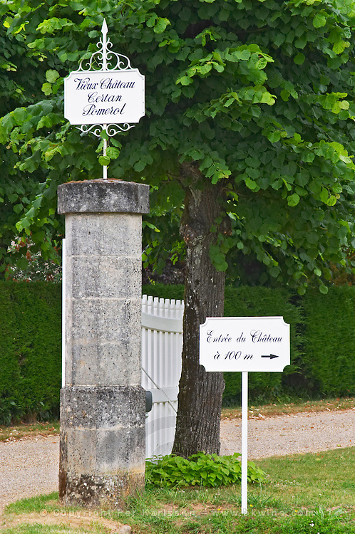 """A white wooden gate and a stone gate post with signs saying Vieux Chateau Certan and """"Entree du Chateau a 100 m"""" (Entry to the chateau at 100 metres to the right)  Pomerol  Bordeaux Gironde Aquitaine France"""
