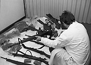 Garda Arms Find.1982.02.02.1982..02.02.1982.2nd February 1982.Image taken at Garda Headquarters Phoenix Park ,Dublin. .Gardai display  their find of Firearms, ammunition and explosives   ..The haul which included armalite rifles also included a poster depicting the 1981 Hunger Striker, Kieran Doherty. Here a technician examines one of the rifles found.