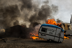 October 26, 2016 - Calais, France - A Caravan stands in the Calais 'Jungle' in front of a burning hut. Huge fires destroyed a mayor part of the refugee camp today. (Credit Image: © Markus Heine/NurPhoto via ZUMA Press)