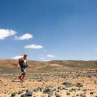 26 March 2007:  #313 Dominique Chauvelier of France runs across a very rocky plain during the second stage (21.7 miles) of the 22nd Marathon des Sables between Khermou and jebel El Otfal. The Marathon des Sables is a 6 days and 151 miles endurance race with food self sufficiency across the Sahara Desert in Morocco. Each participant must carry his, or her, own backpack containing food, sleeping gear and other material.