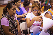 """18 AUGUST 2012 - PHOENIX, AZ:  A woman and her daughter go over the paper required to apply for the """"deferred action"""" program during a deferred action workshop in Phoenix. More than 1000 people attended a series of 90 minute workshops in Phoenix Saturday on the """"deferred action"""" announced by President Obama in June. Under the plan, young people brought to the US without papers, would under certain circumstances, not be subject to deportation. The plan mirrors some aspects the DREAM Act (acronym for Development, Relief, and Education for Alien Minors), that immigration advocates have sought for years. The workshops were sponsored by No DREAM Deferred Coalition.  PHOTO BY JACK KURTZ"""