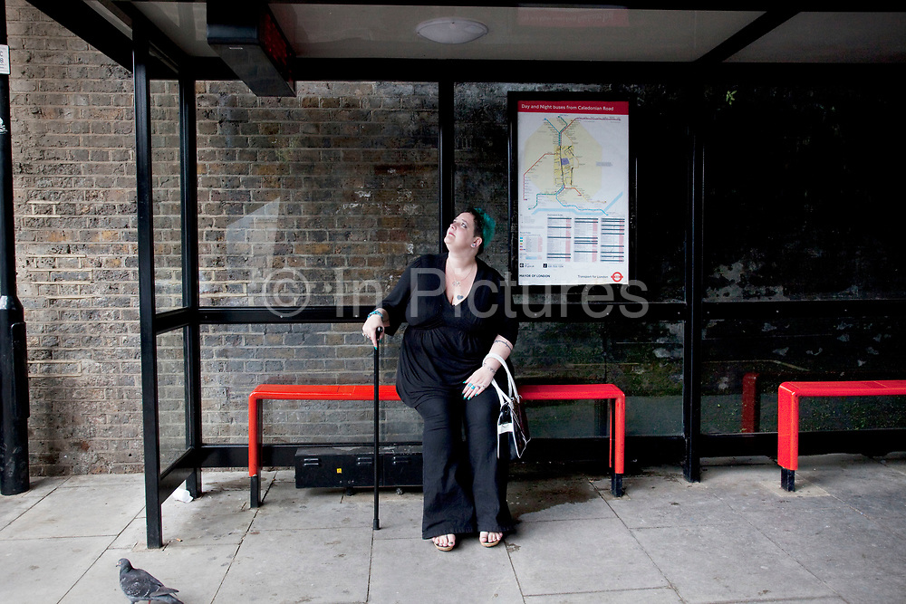 LONDON, ENGLAND, UK, JUNE 18TH 2011. Mother Louise Irwin-Ryan waiting for a bus at the bus stop in her neighbourhood of Barnsbury, near to Kings Cross, North London. Louise is on various benefits to help support her family income, and housing, although recent government changed to benefits may affect her family drastically, possibly meaning they may have to move out of London. Louise Ryan was born on the Wirral peninsula in 1970.  She moved to London with her family in 1980.  Having lived in both Manchester and Ireland, she now lives permanently in North London with her husband and two children. Through the years Louise has battled to recover from a serious motorcycle accident in 1992 and has recently been diagnosed with Bipolar Affective Disorder. (Photo by Mike Kemp/For The Washington Post)