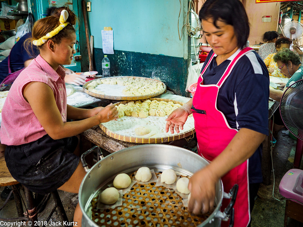 """12 FEBRUARY 2018 - BANGKOK, THAILAND: Women put buns into a steaming tray in a home that makes steamed Chinese buns, called """"bao"""" in the Chinatown neighborhood of Bangkok. Bao are eaten at midnight on the Lunar New Year and served to guests during New Year's entertaining. Lunar New Year, also called Tet or Chinese New Year, is 16 February this year. The coming year will be the Year of the Dog. Thailand has a large Chinese community and Lunar New Year is widely celebrated in Thailand, especially in Bangkok and large cities with significant Chinese communities.    PHOTO BY JACK KURTZ"""