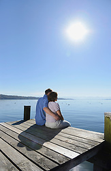Mature couple sitting and embracing each other on boardwalk, Bavaria, Germany