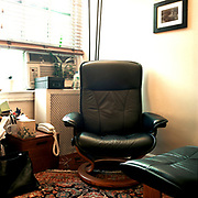 """A black """"Stressless"""" chair and footrest in the corner of a small space, in front of a window, raidiator, and air conditioner, with plants and other things on the raidiator cover. There is an oriental carpet covering most of the floor, and a large bag and other things in the left edge of the frame."""