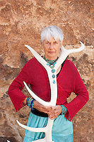 Portrait of a strong and fierce senior woman holding an Elk antler wearing jewelry by Art Medicine Adornment.