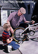 Active Aging Senior Citizens, Retired, Activities, Grandfather and Grandson Activities, Loving Relationship, Grandfather helps repair Grandson's Bicycle