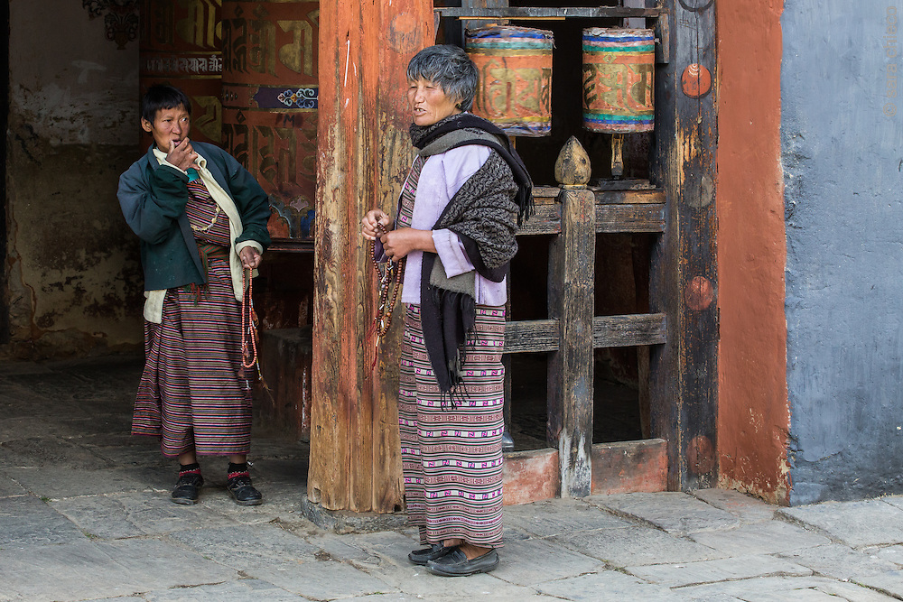 Buddhist Pilgrims walk the perimeter of Jambay Lhakhang and turn the prayer wheels, Jakar, Bumthang, Bhutan