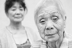 Black and white portrait photograph of Asian old granny who is afraid while daughter watches in background