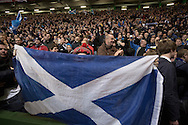 A home supporter obscured by a Scottish saltire flag reacting with delight at the final whistle of the European Championship qualifying match between Scotland and the Republic of Ireland at Celtic Park, Glasgow. Scotland won the match by one goal to nil, scored by Shaun Maloney 16 minutes from time. The match was watched by 55,000 at Celtic Park, the venue chosen to host the match due to Hampden Park's unavailability following the 2014 Commonwealth Games.